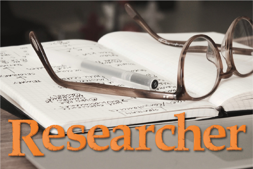 A pair of glasses sit on top of a book with the label Music Researcher